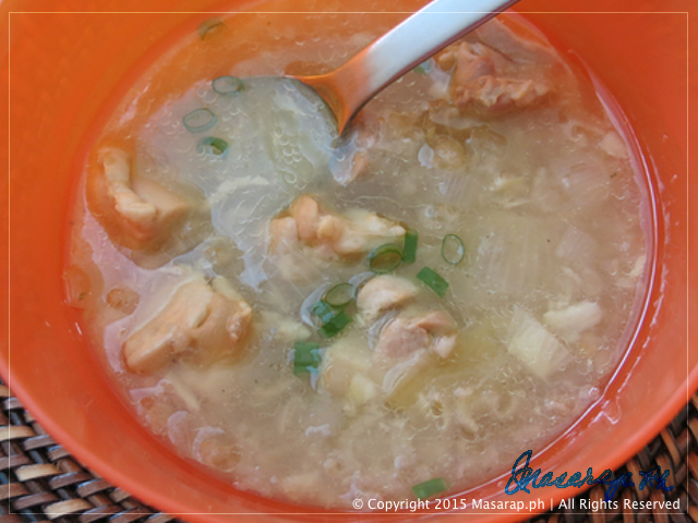 arroz caldo manok in an orange bowl with a spoon